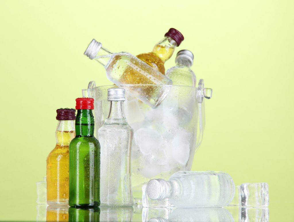 Minibar bottles in bucket with ice cubes