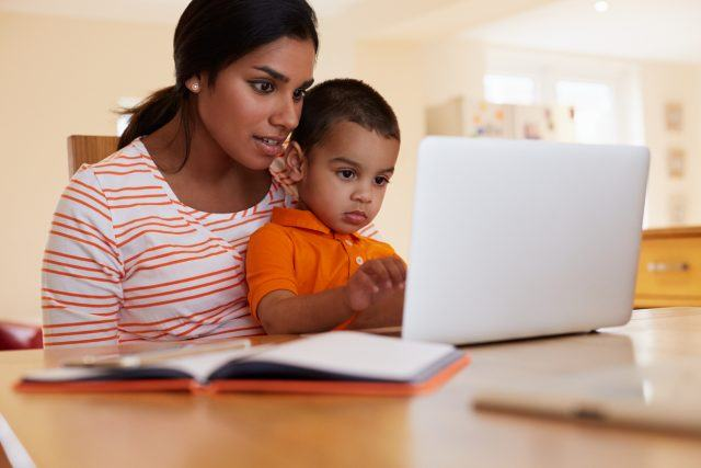 Mother and son book a flight on their laptop