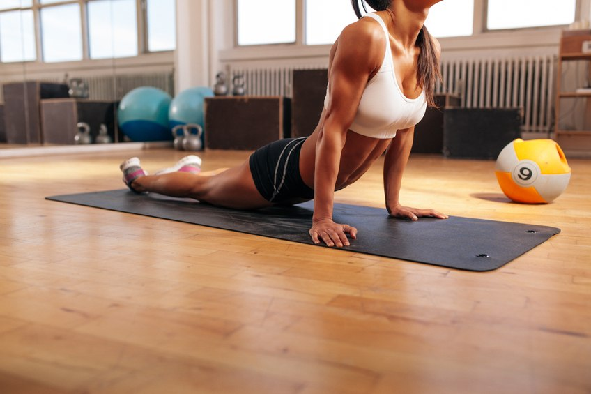 young woman stretching her stomach on fitness mat