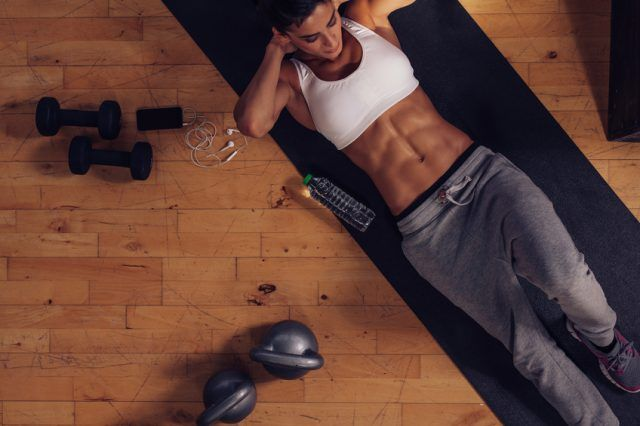 Sporty young woman lying on exercise mat doing sit-ups.
