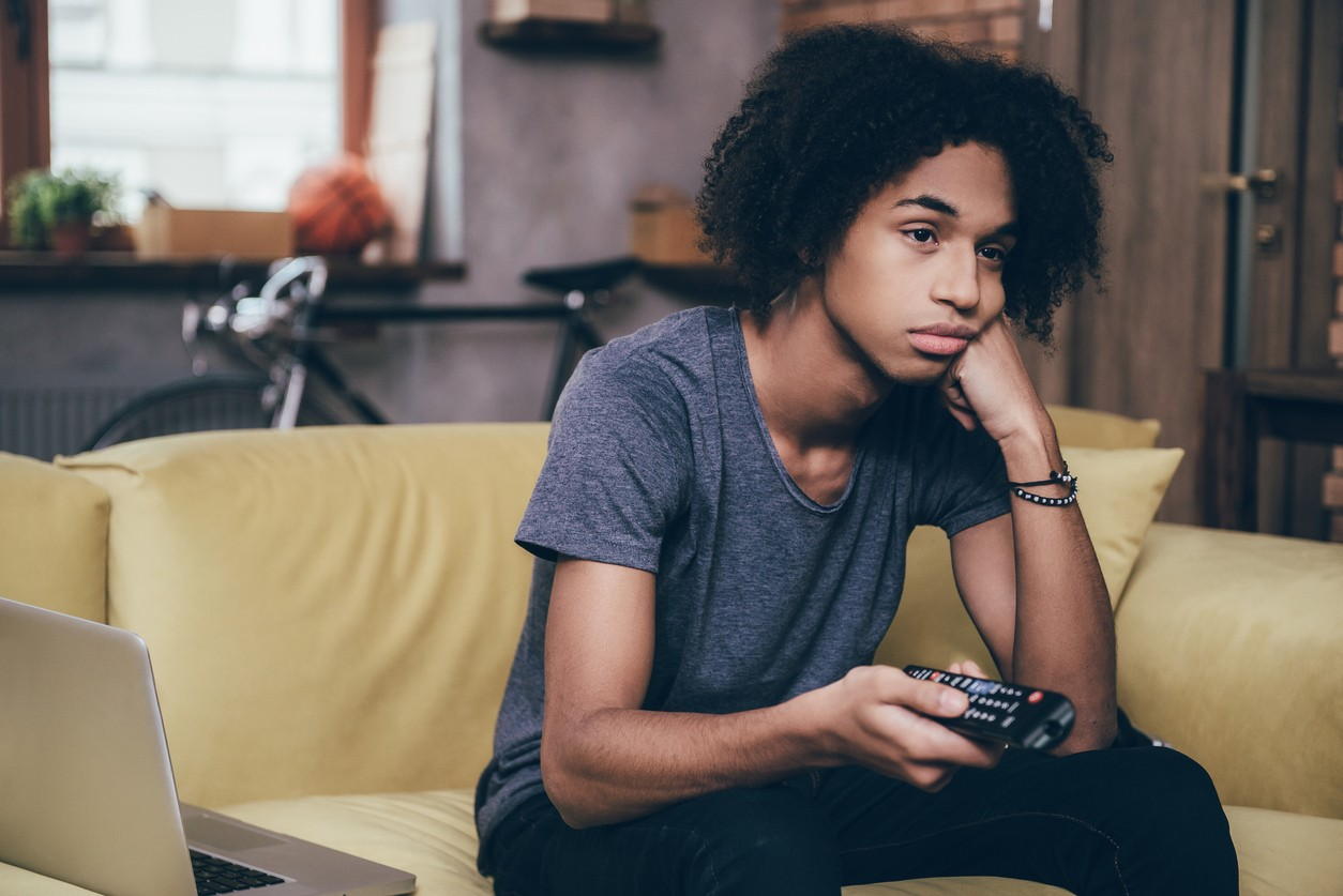 African man holding remote control and looking bored