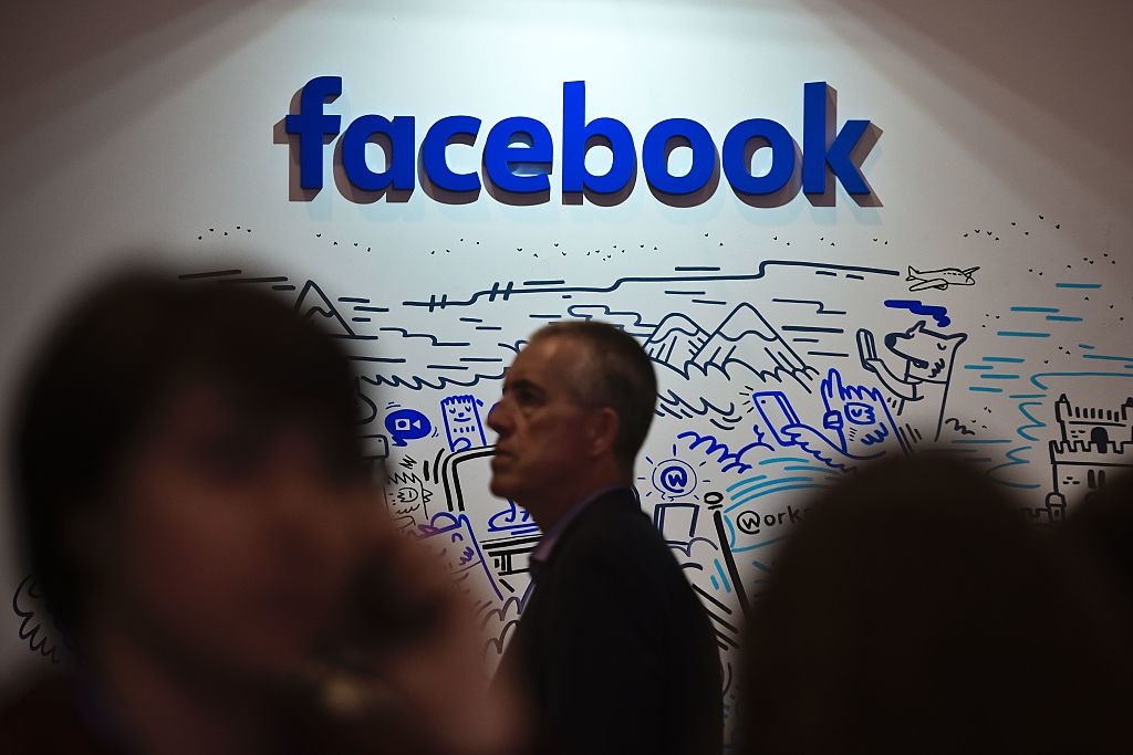People pass by an artwork by artist Geo Law at Facebook's space during the Web Summit at Parque das Nacoes, in Lisbon on November 9, 2016.