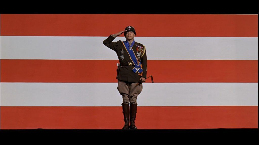 General Patton in uniform saluting in front of an orange and white striped background