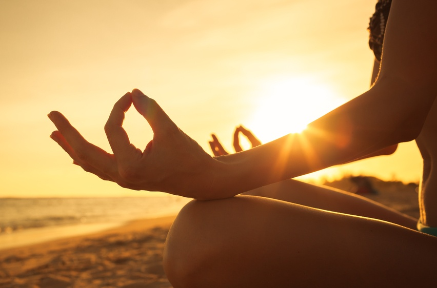 Woman meditating on the beach in front of the sun.