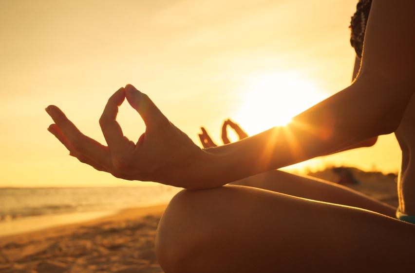 Femme méditant sur la plage devant le soleil.
