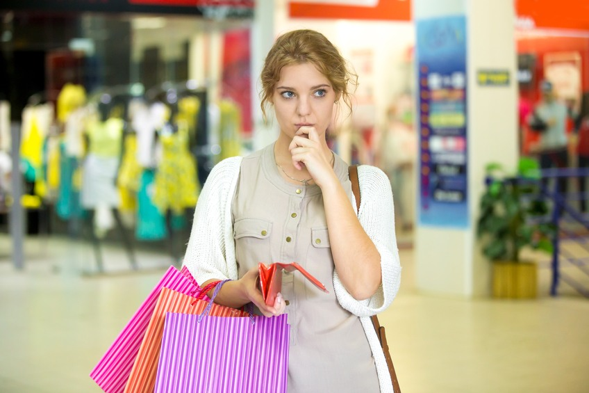 A woman, shopping for clothes, considers a purchase