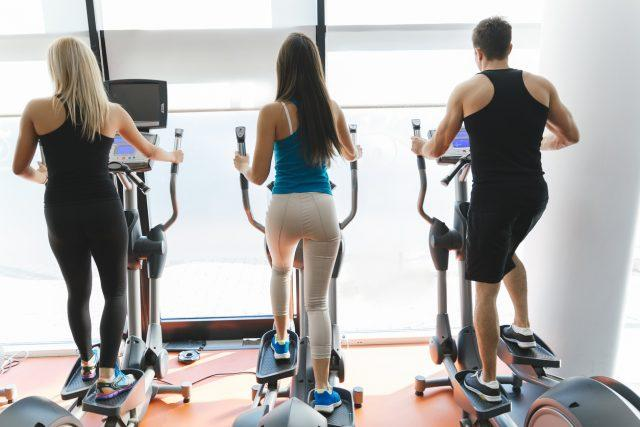 People exercising on elliptical machines at a gym.
