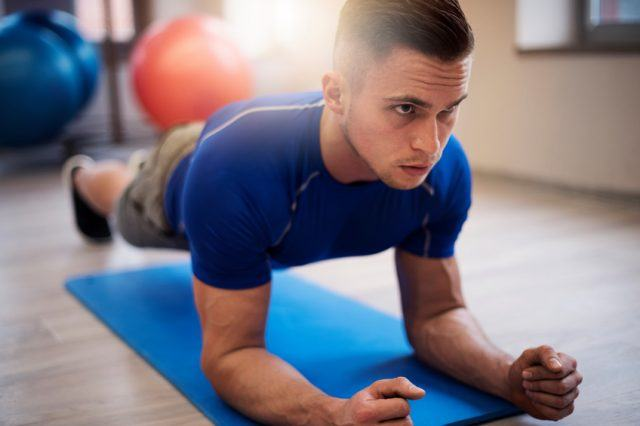 Young man doing planks on a blue mat.