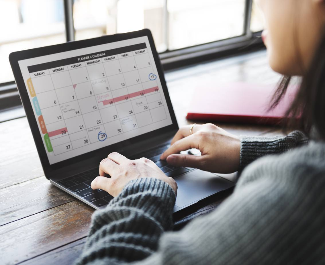 Woman using planner on laptop