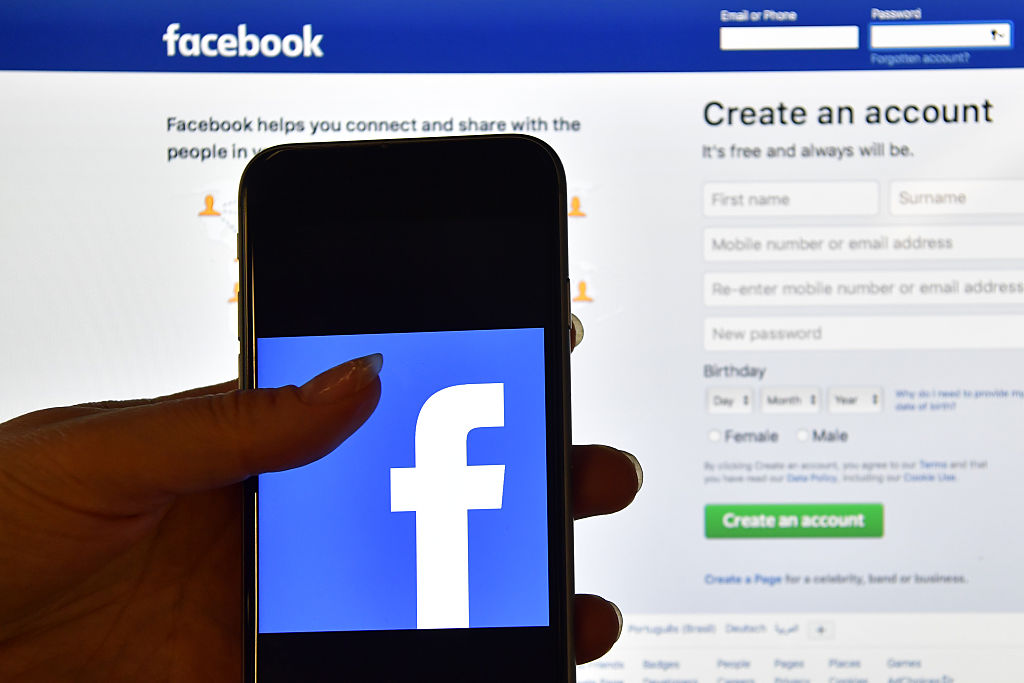 A person holds an iPhone displaying the Facebook app logo in front of a computer screen