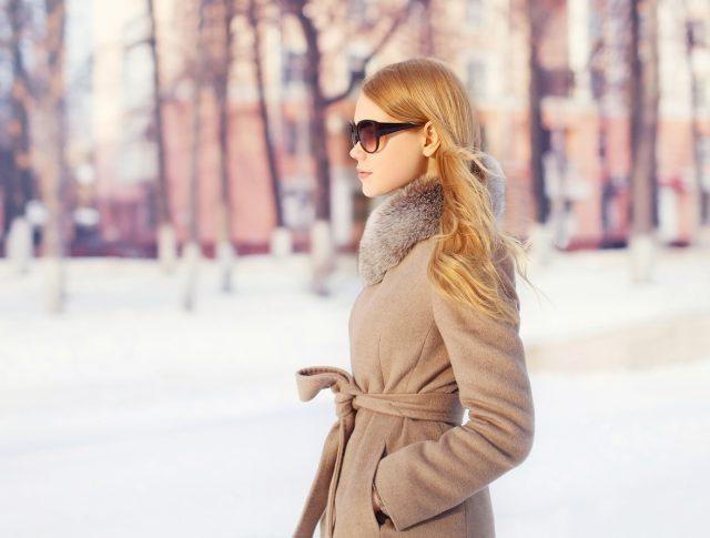beautiful elegant woman wearing a coat jacket and sunglasses in city