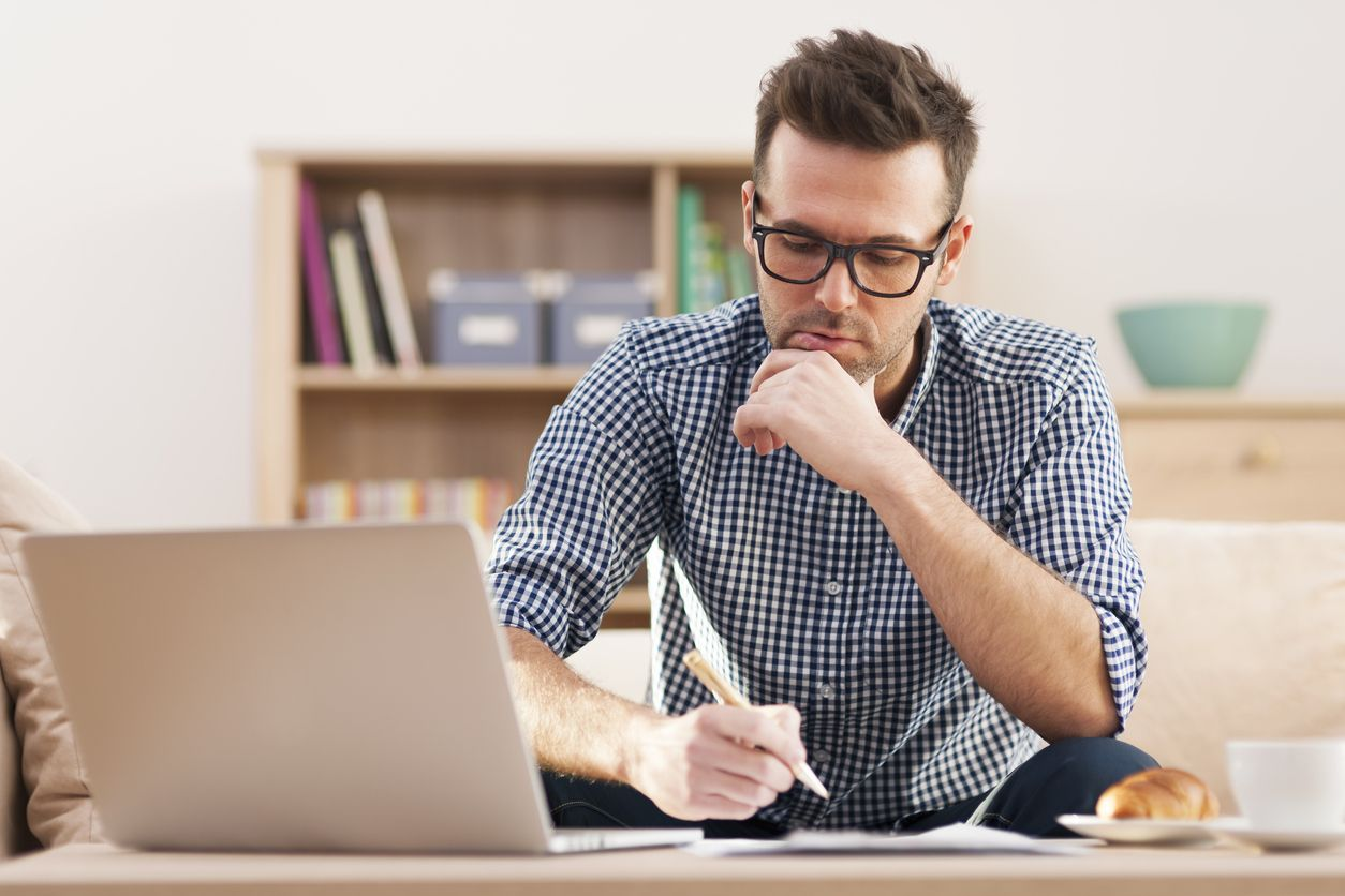 A focused man working on goal-setting at home