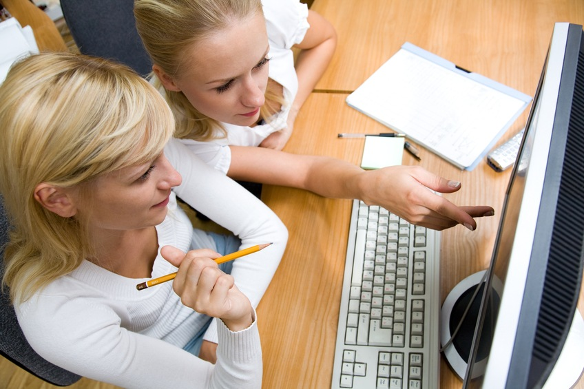 two women working on a computer together