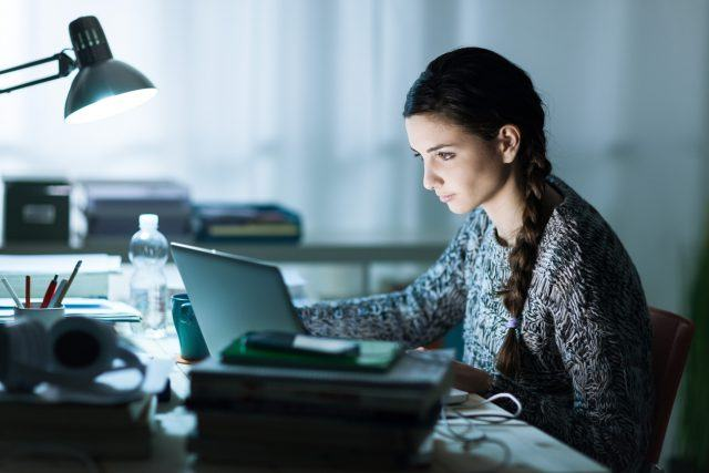 young student sitting at desk and doing her homework