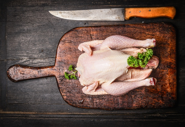 Raw whole chicken with knife