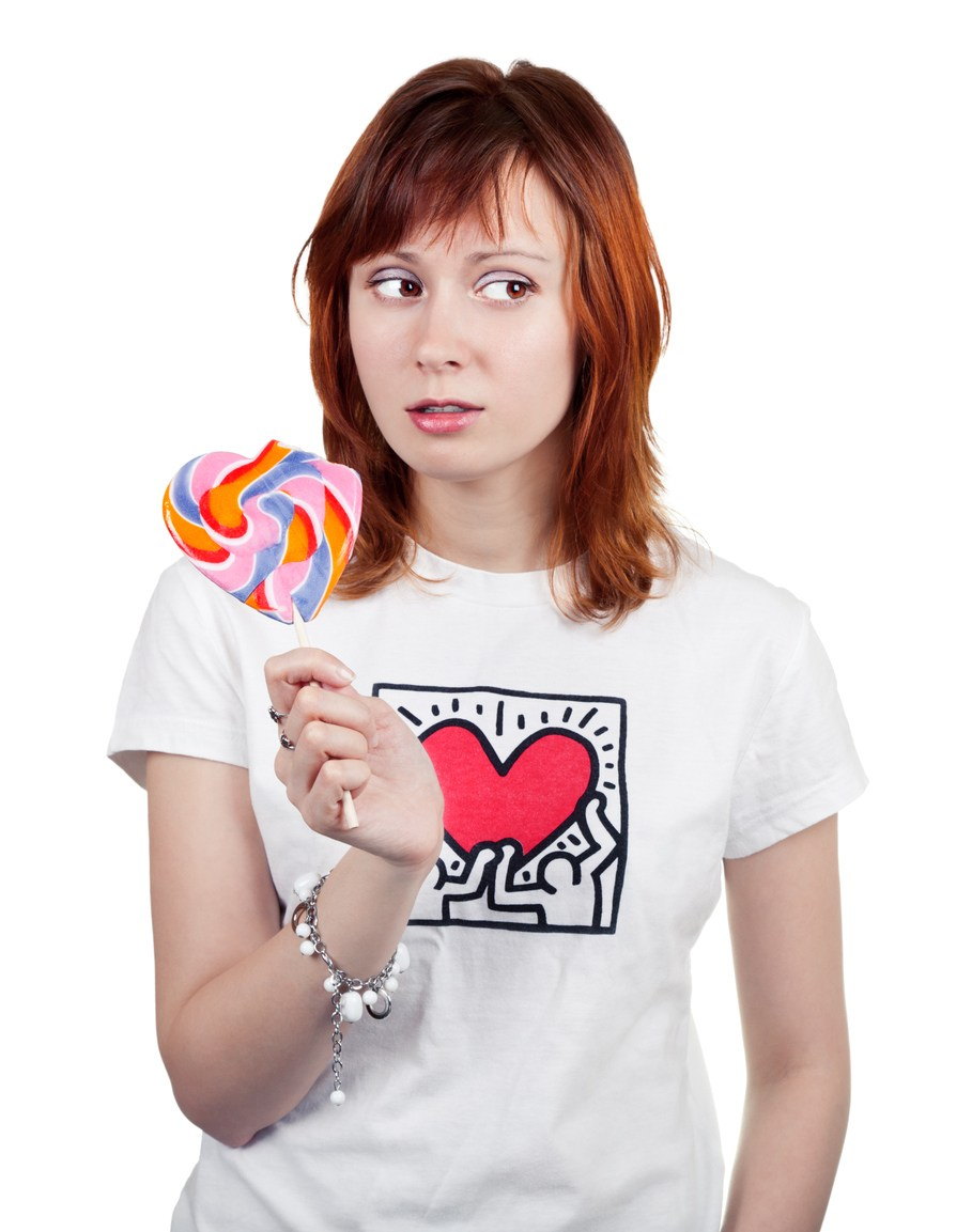red-haired young woman with a colorful candy