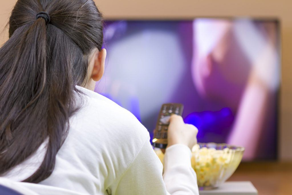Teenager girl eating and watching tv