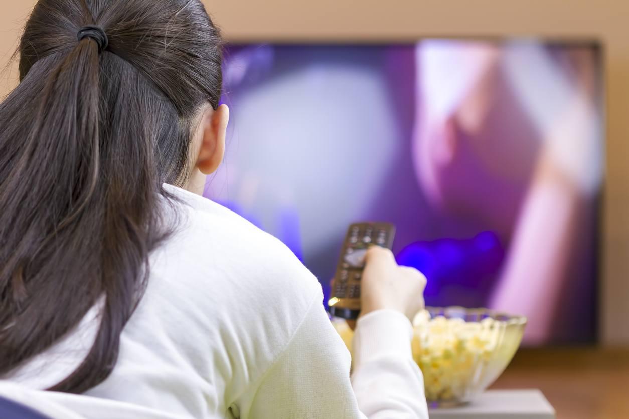Teenager girl eating and watching tv
