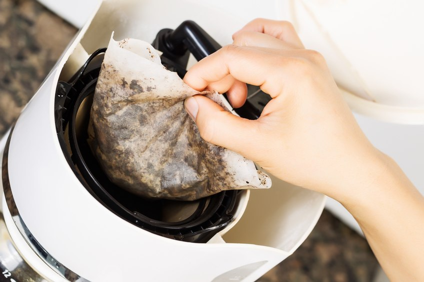 female hand pulling out used coffee filter