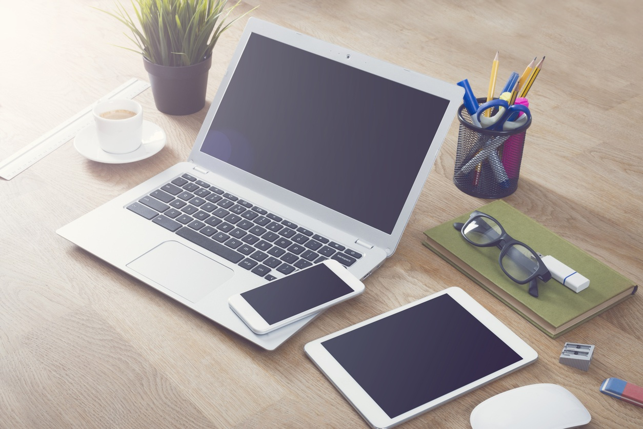 Laptop, smartphone, tablet with other desk items and coffee on table