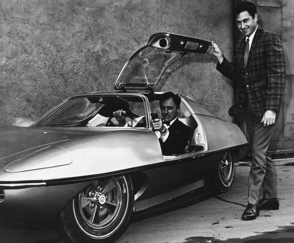 Portrait of actor Robert Vaughn sitting in the new car designed for his television show 'The Man From UNCLE', with the cars designer Gene Winfield
