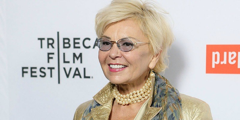 Roseanne Barr is smiling on the red carpet and is wearing glasses.