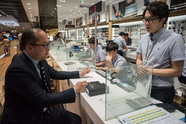 A customer inquires about returning a Samsung Note 7 mobile phone at a Samsung store