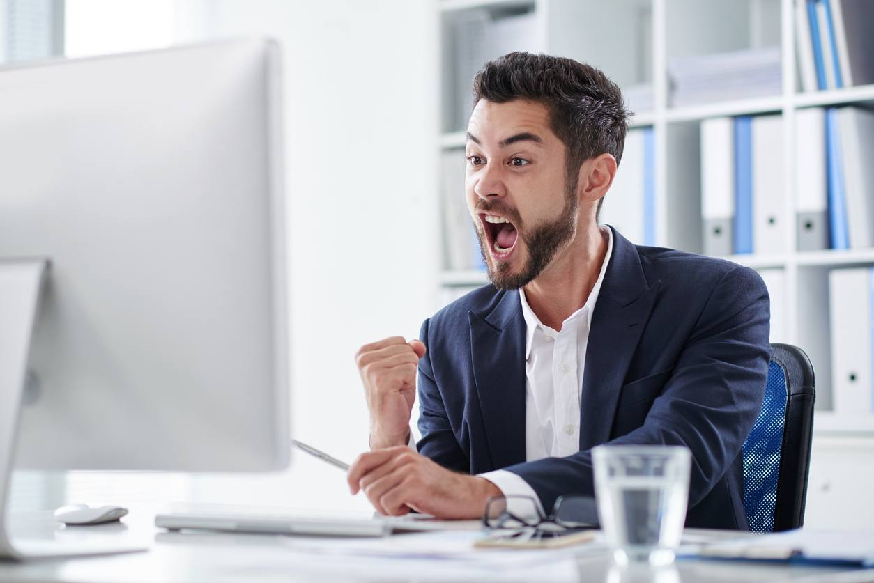 young entrepreneur screaming of joy when looking at computer screen