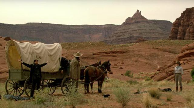 Logan (Ben Barnes), William (Jimmi Simpson) and Dolores (Evan Rachel Wood) stand outside near a covered wagon in a scene from 'Westworld'