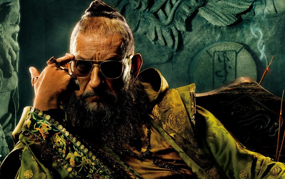 The Mandarin, wearing sunglasses, and pointing to his forward with his right hand