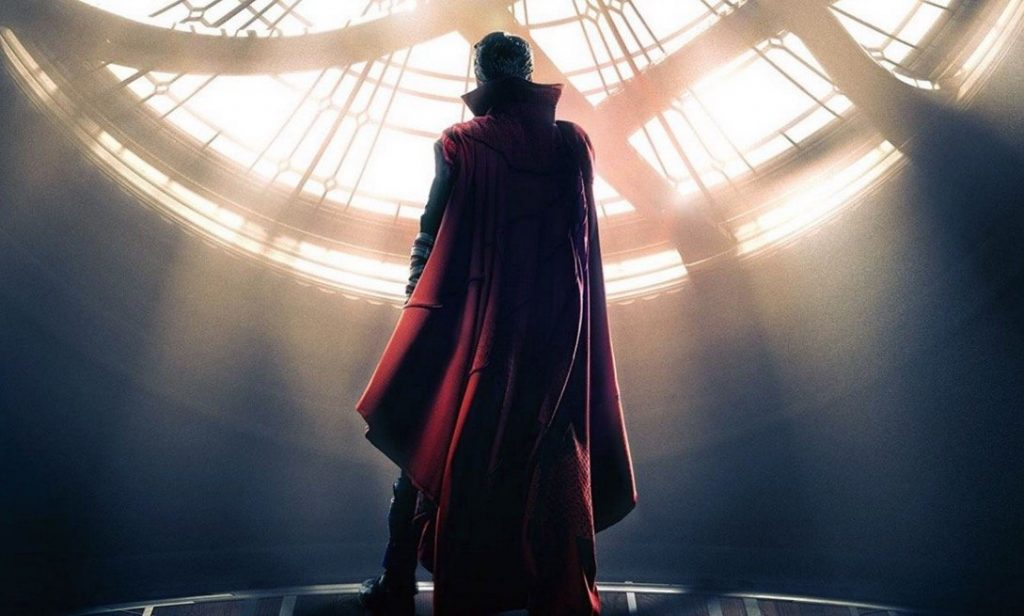 Benedict Cumberbatch stands in front of a window in his cape in a scene from Doctor Strange