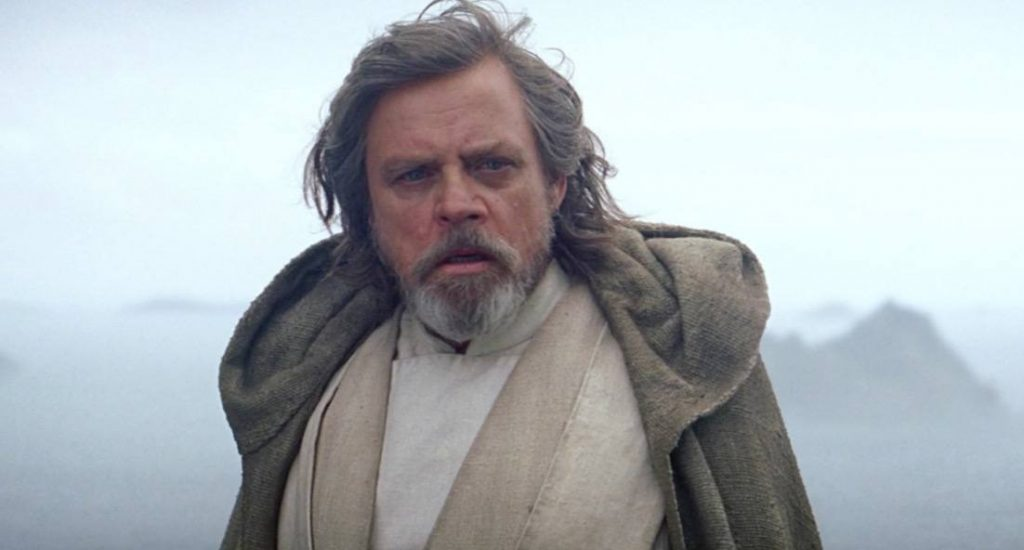 Luke Skywalker at the end of Star Wars: The Force Awakens looking shocked in a tan shirt and jacket