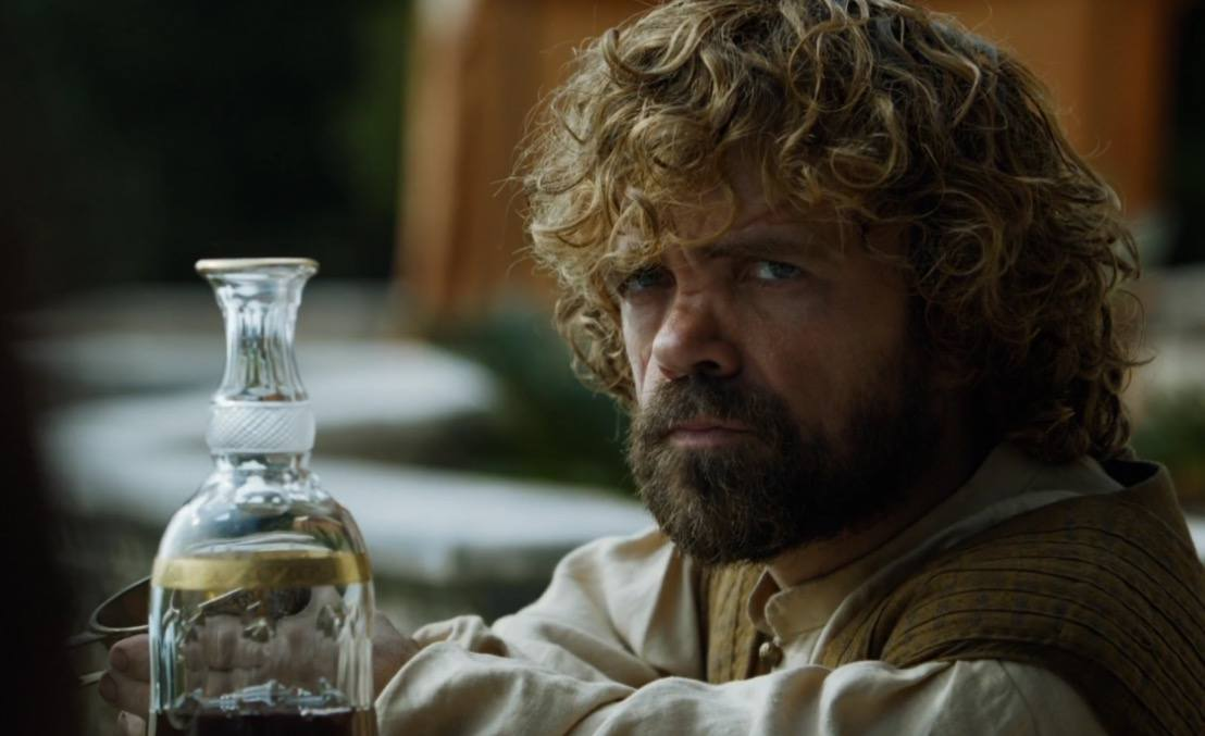 Tyrion scowls with his arms crossed, with an empty carafe of wine sitting on the table next to him