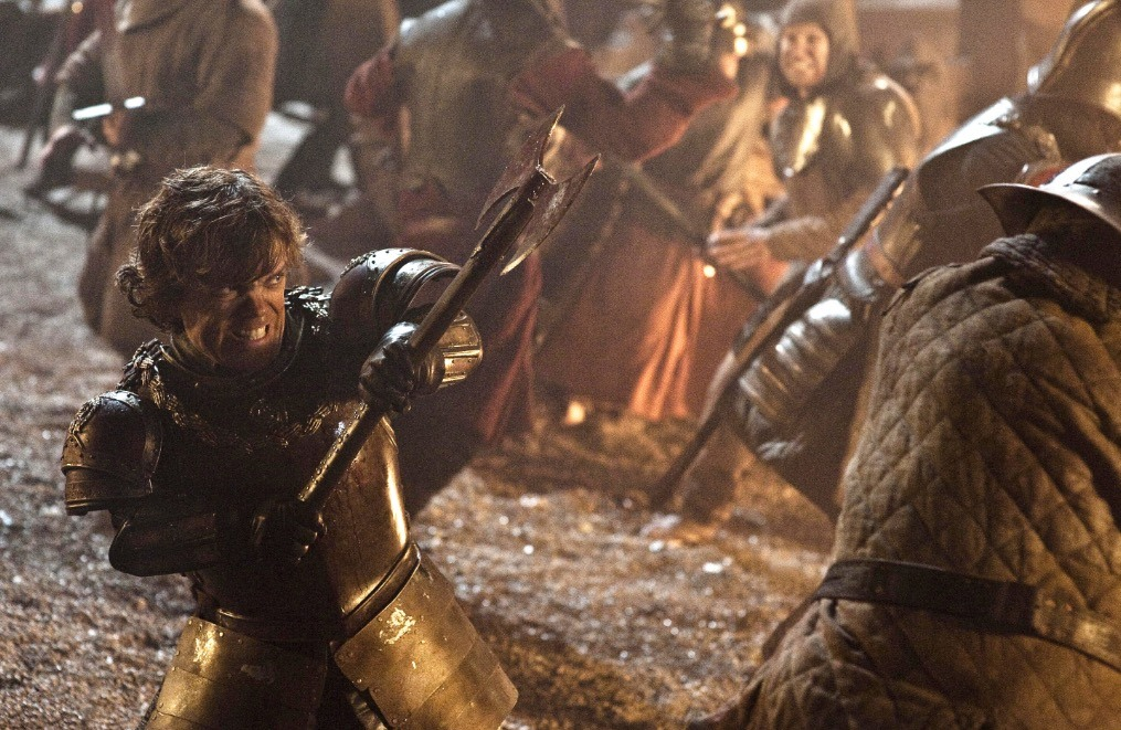 Tyrion yelling angrily, dressed in armor and wielding an ax in the middle of a raging battlefield