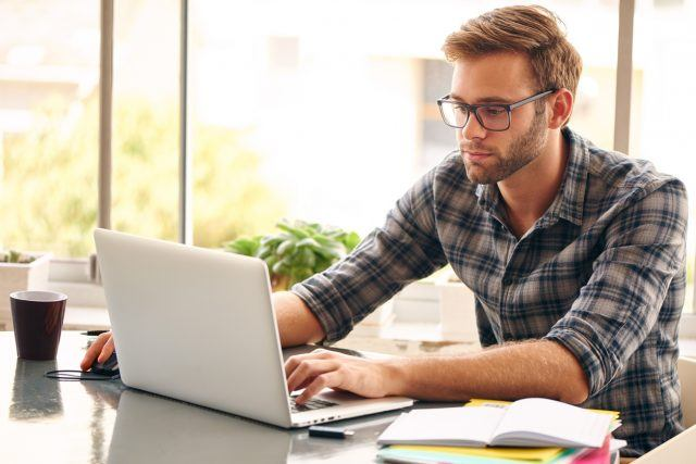 Young man with glasses working on his laptop