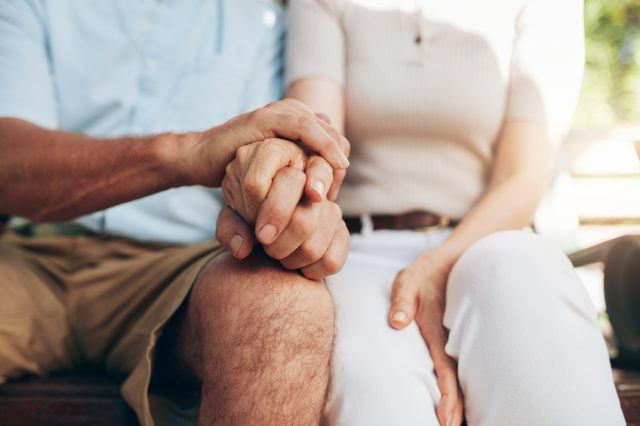 Senior couple holding hands gently