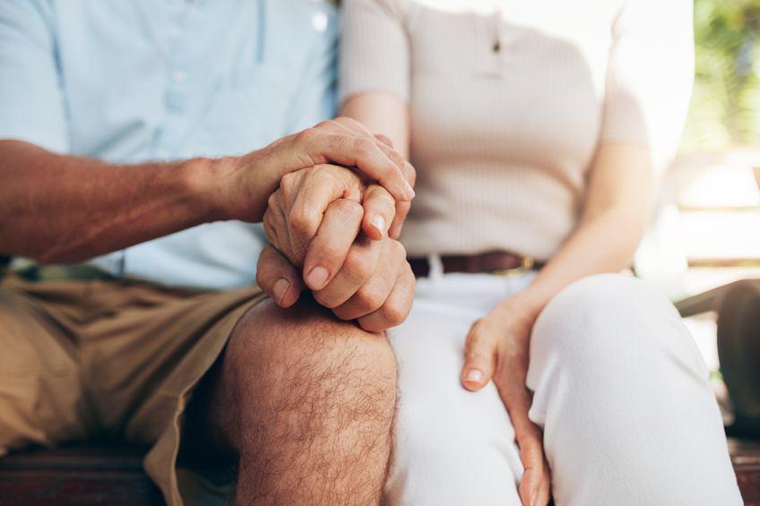Close up shot of senior couple holding hand