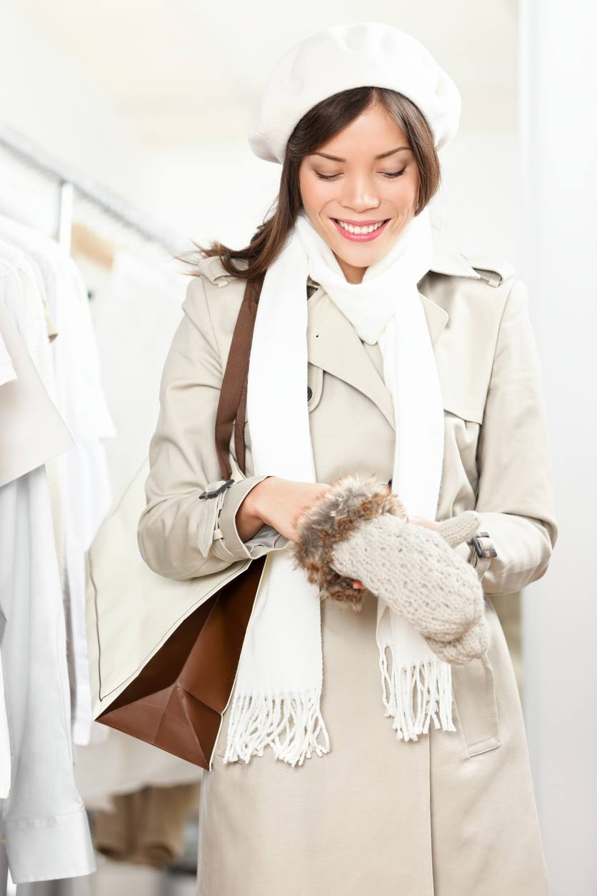 woman trying winter gloves in clothes store