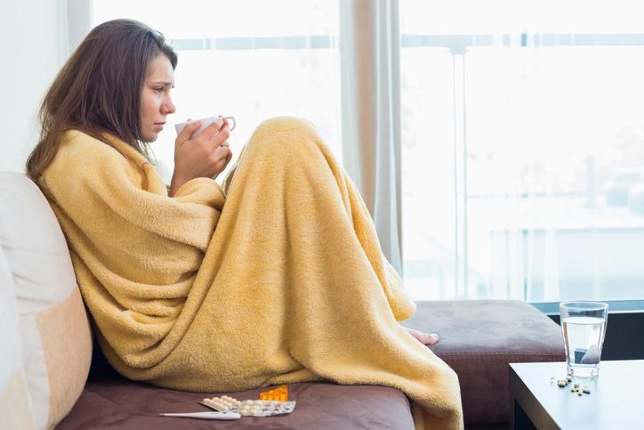 Side view of sick woman having coffee