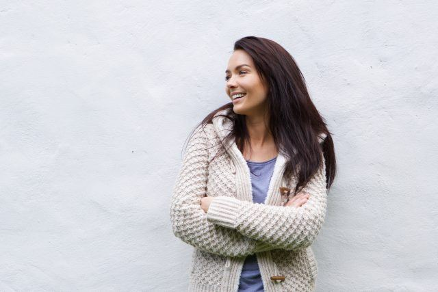 Woman in wool sweater stands outside.