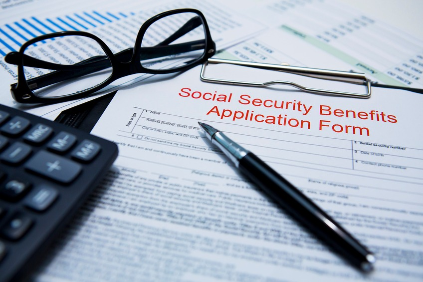Social Security Benefits Application Form with pen and glasses