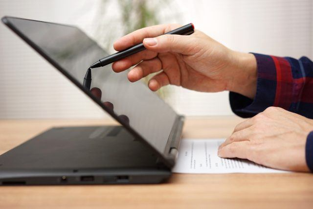 A man working on touchscreen laptop