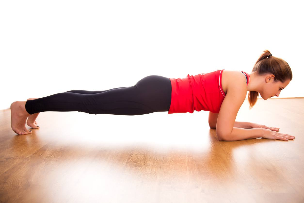 A woman demonstrates a plank