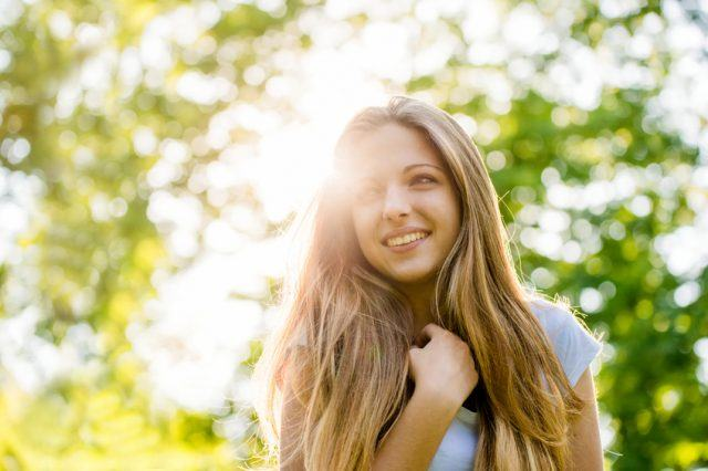 portrait of joyful teen girl taken directly against sun