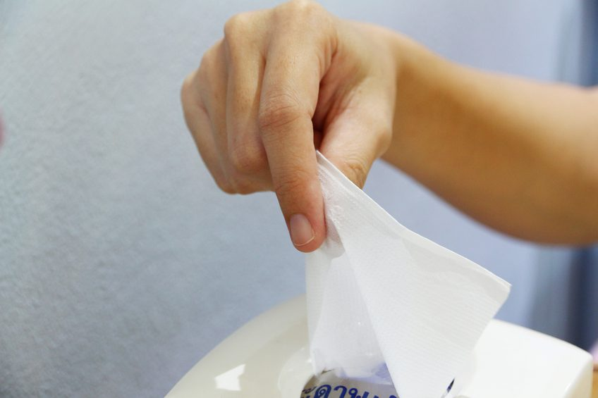 hand pulling tissue out of box