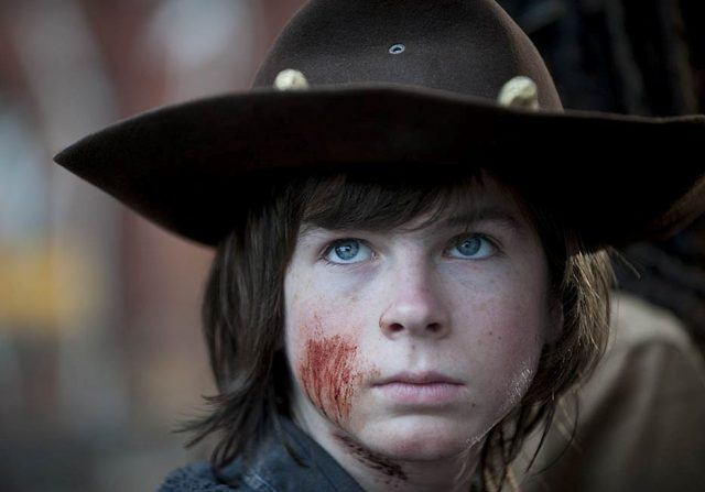 Carl Grimes looking upward while wearing a brown hat.