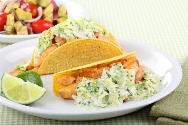 Two fish tacos topped with coleslaw.