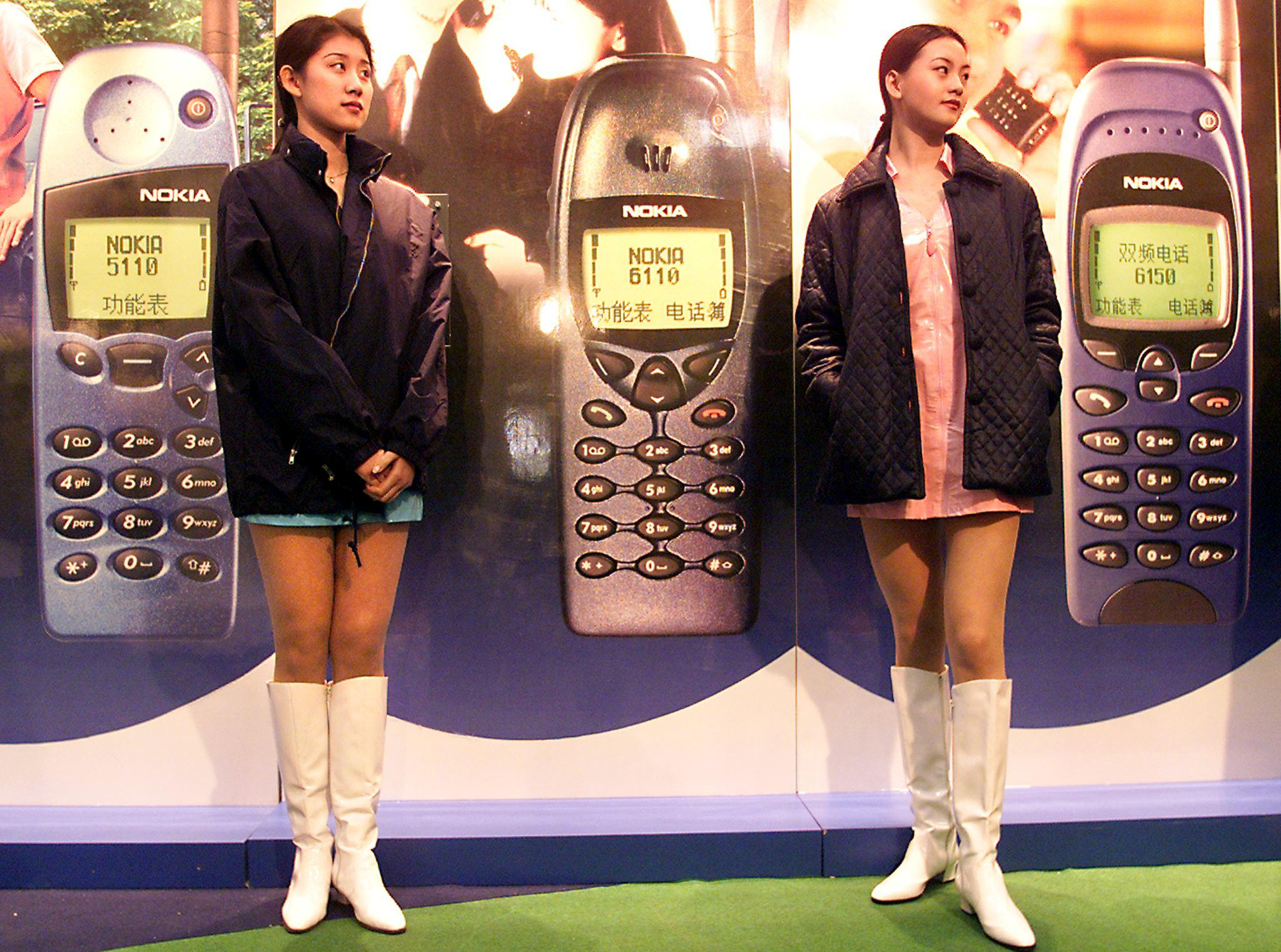 Two young Chinese women working for Nokia stand ready to help customers