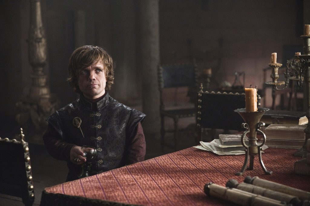 Tyrion wearing a black leather vest, standing in front of a long table and holding a cup of wine