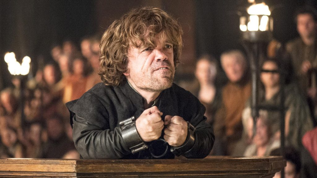 Tyrion Lannister grimaces, as he closes both fists and pulls them in close to his chest, while shackled in chains